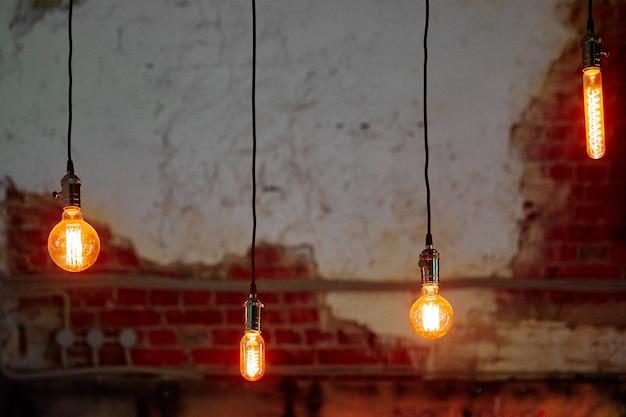 Quatre ampoules allumées de différentes formes suspendues à de longs fils noirs