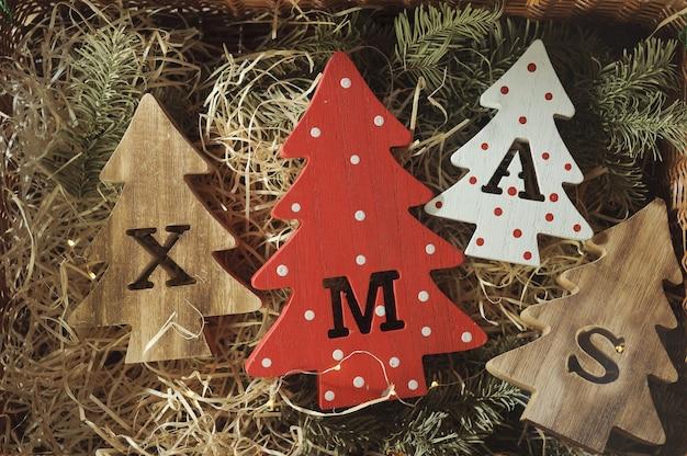 Quatre arbres de noël en bois décoratifs avec des lettres sculptées de noël et des ornements de noël