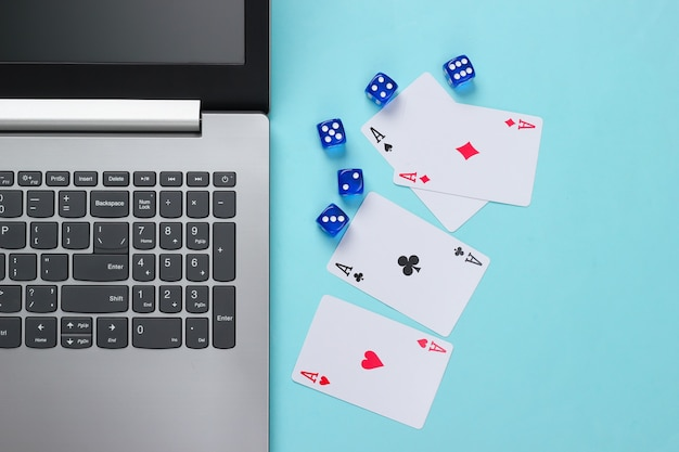 Quatre as, dés et clavier d'ordinateur portable sur une surface bleue. casino de poker en ligne. dépendance au jeu