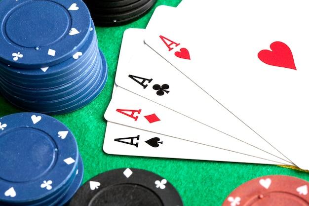 Quatre as et des jetons de poker empilés de plusieurs couleurs