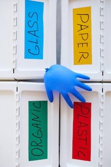 Quatre bacs en plastique étiquetés pour le stockage et le tri des déchets à la maison, avec un gant en caoutchouc soufflé sur le dessus