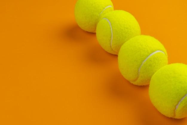 Quatre balles de tennis sur une orange