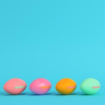 Quatre ballons de football américain colorés sur fond bleu clair