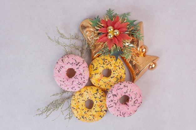 Quatre beignets sucrés colorés sur tableau blanc.