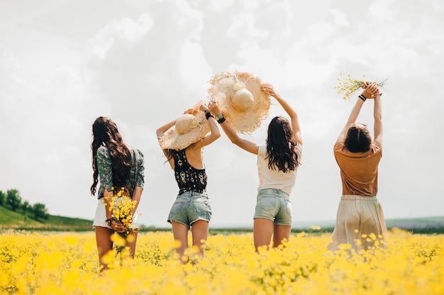 Quatre belle fille hippie dans un champ de fleurs jaunes