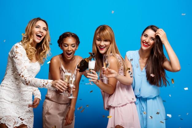 Quatre belles filles se reposant à la fête sur le mur bleu