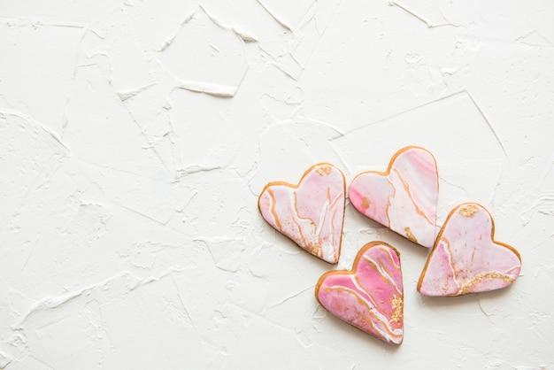 Quatre biscuits en forme de coeurs en marbre blanc sur mur en bois