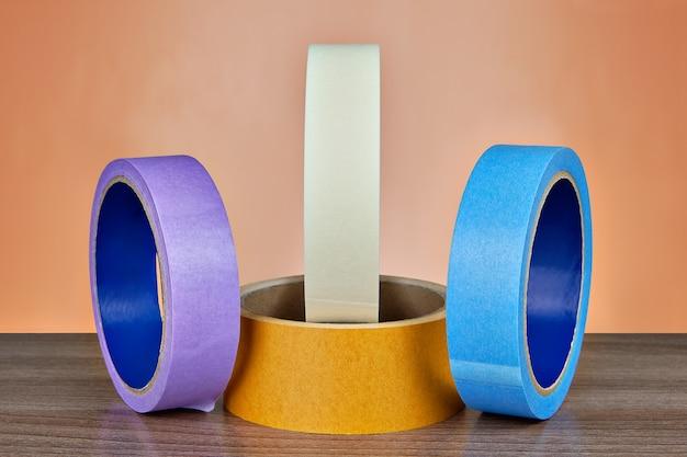 Quatre bobines de ruban adhésif multicolore.