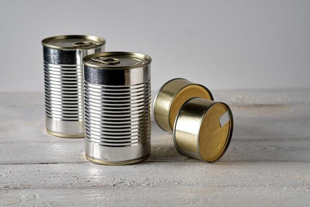 Quatre boîtes de conserve sur table en bois blanc