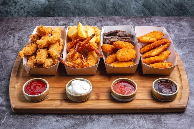 Quatre boîtes de pépites avec du fromage de crevettes au poulet et du poisson avec quatre sauce