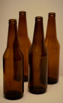 Quatre bouteilles de bière vides sombres sur la table