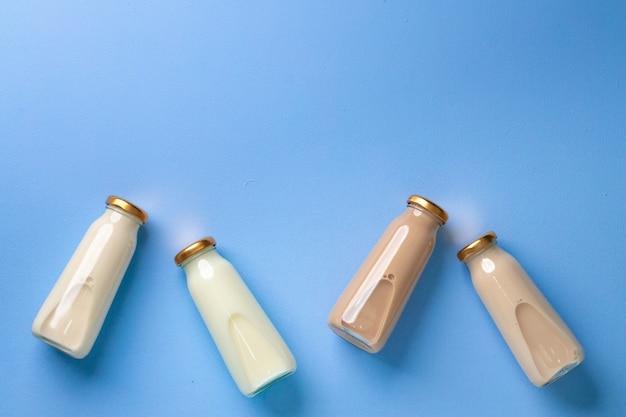Quatre bouteilles en verre de lait aromatisé sur flatlay bleu