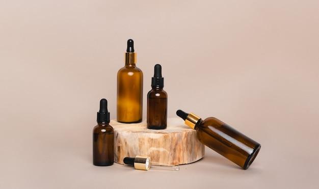 Quatre bouteilles en verre marron avec pipettes sur podium en bois isolé sur fond beige
