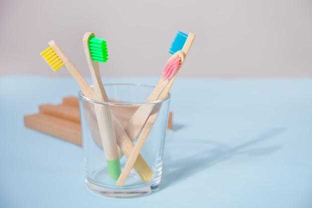 Quatre brosses à dents colorées éco bambou kid dans un support sur la surface bleue