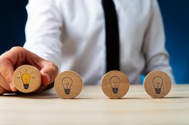 Quatre cercles en bois avec des symboles d'ampoule sur eux dans une rangée avec un homme d'affaires ramassant celui avec une ampoule incandescente.