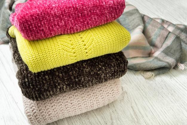 Quatre chandails de couleurs chaudes sur un fond en bois
