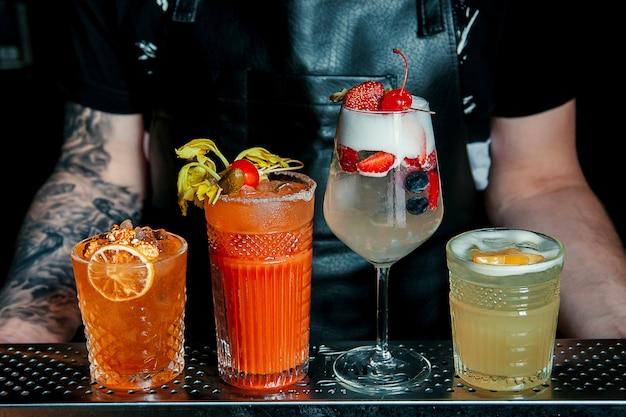 Quatre cocktails frowzen sur table avec des fruits savoureux sur fond de grenier.