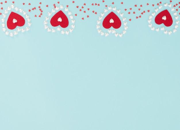 Quatre coeurs de feutre rouge à l'intérieur d'un cœur fait de petits coeurs de perles sur bleu