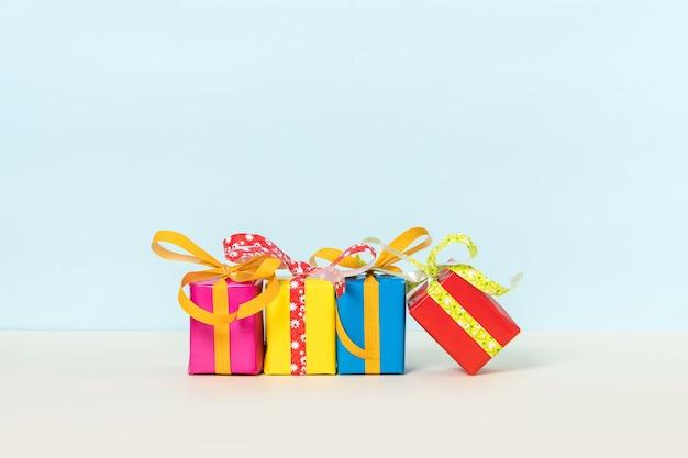 Quatre coffrets cadeaux colorés sur fond pastel.