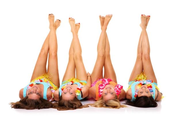 Quatre copines allongées sur le sol en jupes hawaïennes avec leurs jambes sur blanc