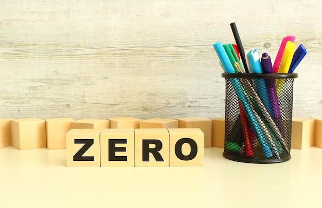 Quatre cubes en bois empilés avec les lettres zéro sur un bureau blanc sur fond gris.