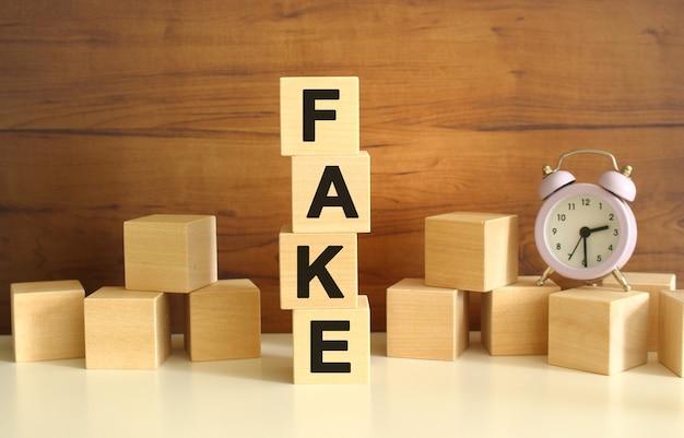 Quatre cubes en bois empilés verticalement sur un fond marron forment le mot fake.
