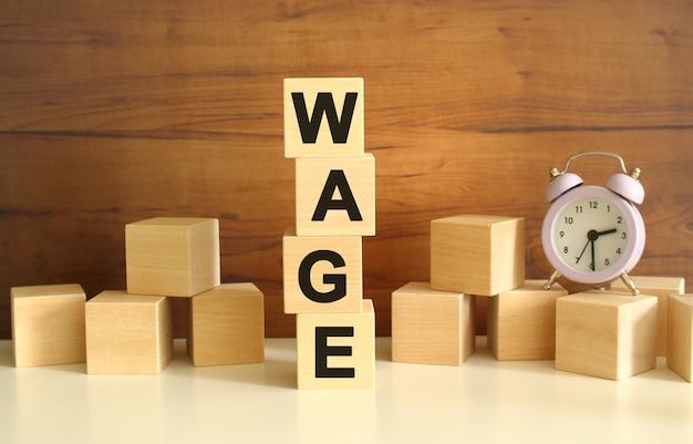 Quatre cubes en bois empilés verticalement sur fond marron forment le mot salaire. des cubes sont dispersés à proximité et il y a une horloge. concepts de vue de face