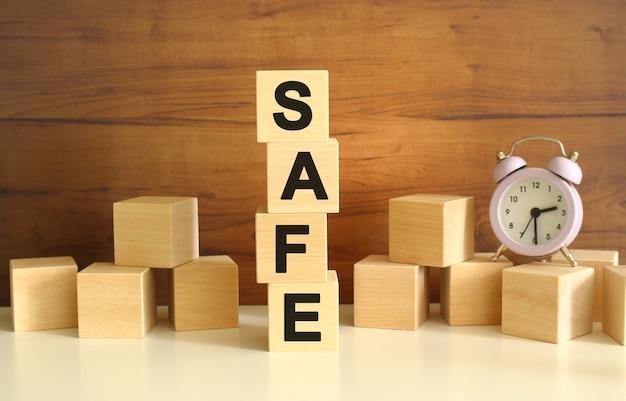 Quatre cubes en bois empilés verticalement sur un fond marron forment le mot sécurité. des cubes sont dispersés à proximité et il y a une horloge. concepts de vue de face