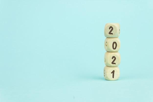 Quatre cubes de jouets en bois disposés verticalement sur fond bleu avec texte 2021, concept de croissance et de gestion de l'entreprise.