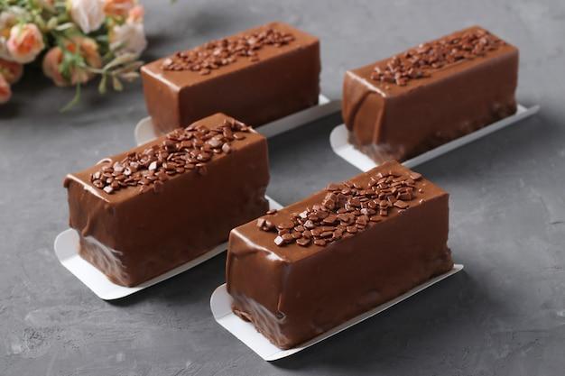 Quatre desserts mousse recouverts de chocolat sur un gros plan de fond gris foncé.
