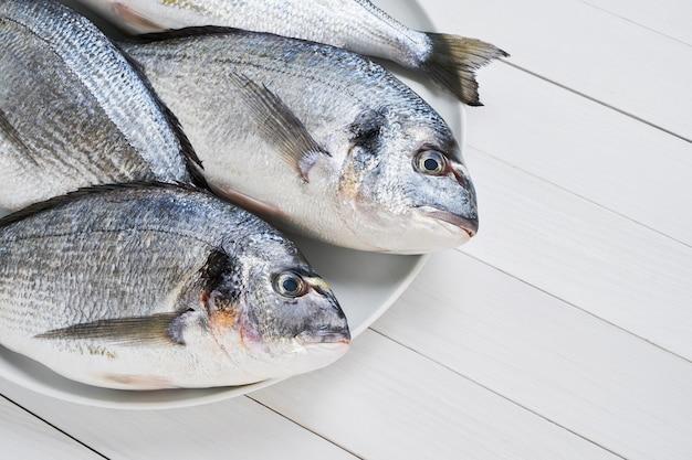 Quatre dorades royales fraîches sur un plat sur un tableau blanc. concept de nourriture saine. copiez l'espace. concept de fruits de mer méditerranéens.