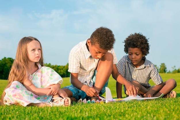Quatre enfants heureux jouent avec un jouet d'avion et peignent