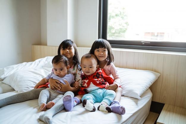 Quatre enfants sourient assis sur le lit