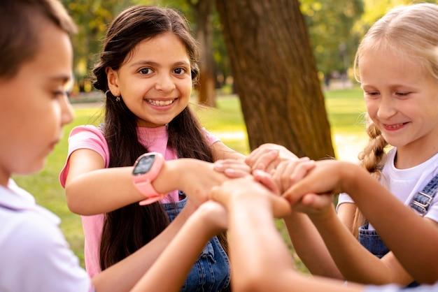 Quatre enfants tenant à la main dans un parc