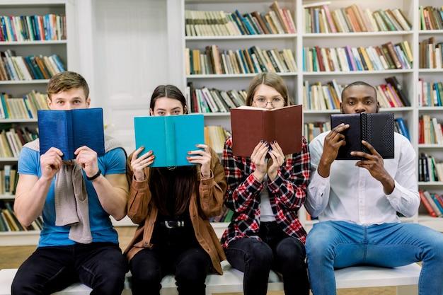 Quatre étudiants amis multiethniques, deux garçons et deux filles en tenue décontractée, cachant des visages derrière des livres ouverts
