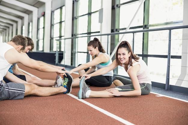 Quatre femmes et hommes sportifs s'étirent sur une piste de course