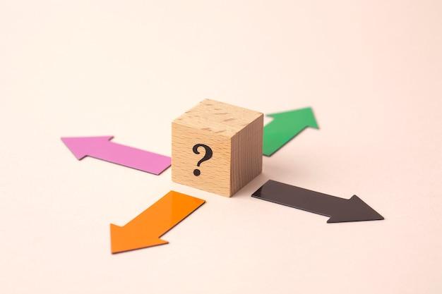 Quatre flèches de direction avec un point d'interrogation sur le cube en bois