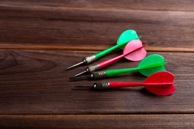 Quatre fléchettes colorées sur un fond en bois. atteindre la cible