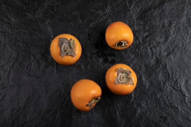 Quatre fruits kaki mûrs placés sur une surface noire