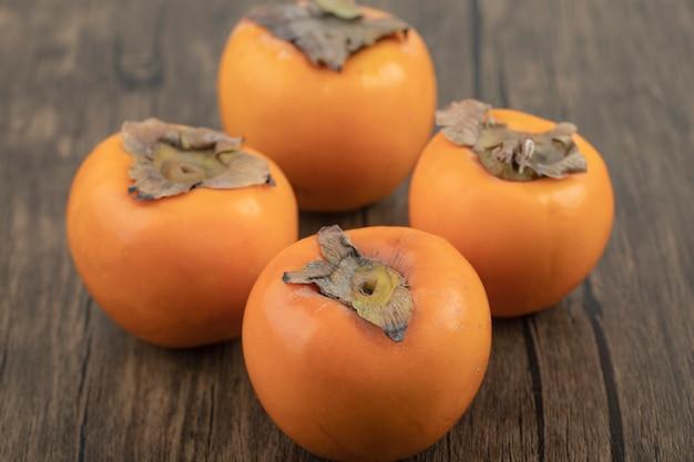 Quatre fruits kakis mûrs placés sur une surface en bois