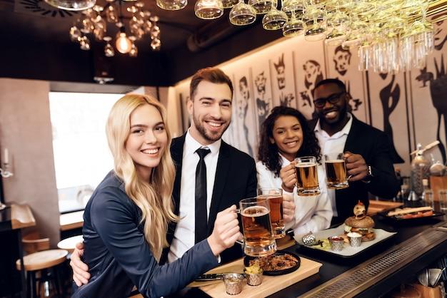 Quatre gars et filles ont commandé une bière au bar.