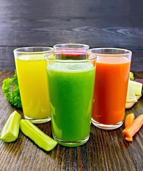 Quatre grands verres avec le jus de carotte, de concombre, de betterave et de citrouille avec des légumes sur fond de planches de bois foncé