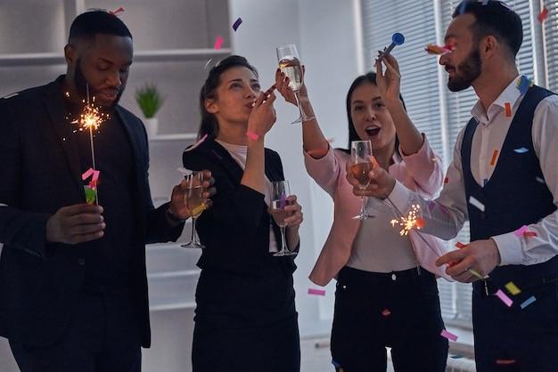 Les quatre hommes d'affaires ayant une fête de bureau avec champagne et confettis