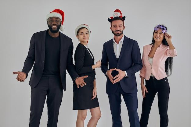 Les quatre hommes d'affaires internationaux debout dans des chapeaux rouges