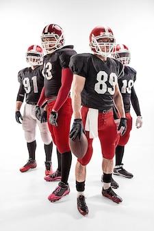 Les quatre hommes de fitness caucasiens en tant que joueurs de football américain posant sur toute la longueur avec un ballon sur fond blanc