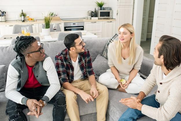 Quatre jeunes amis interculturels jouant au jeu de nom tout en vous relaxant sur un canapé dans le salon tout en se réunissant à la maison