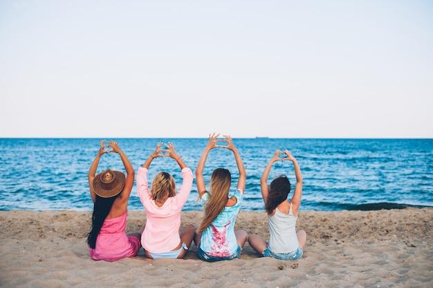 Quatre jeunes chapeaux belle fille assis sur la plage