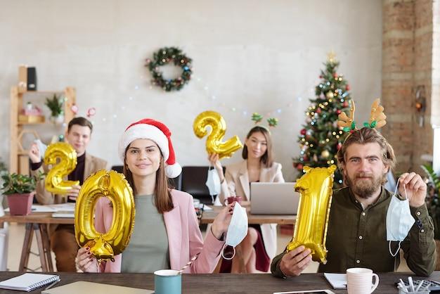 Quatre jeunes employés de bureau dans des accessoires de noël tenant des numéros gonflables de l'année prochaine et des masques de protection pour montrer la fin de l'épidémie de covid