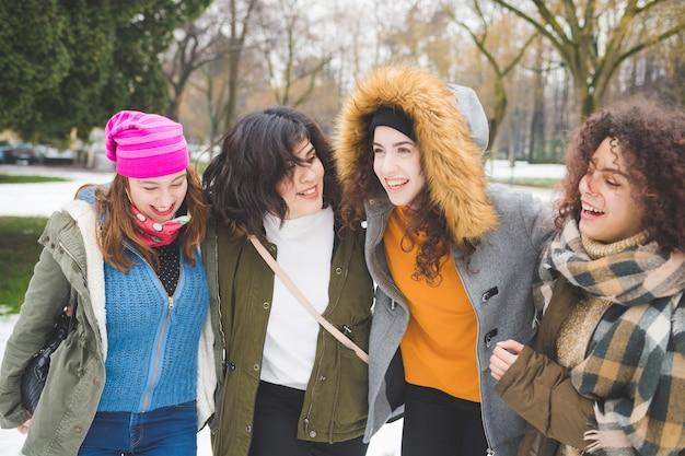 Quatre jeunes femmes multiethniques embrassant le champ de neige en riant