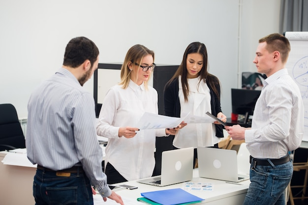 Quatre jeunes gens d'affaires travaillant en équipe se sont réunis autour d'un ordinateur portable dans un bureau moderne à aire ouverte